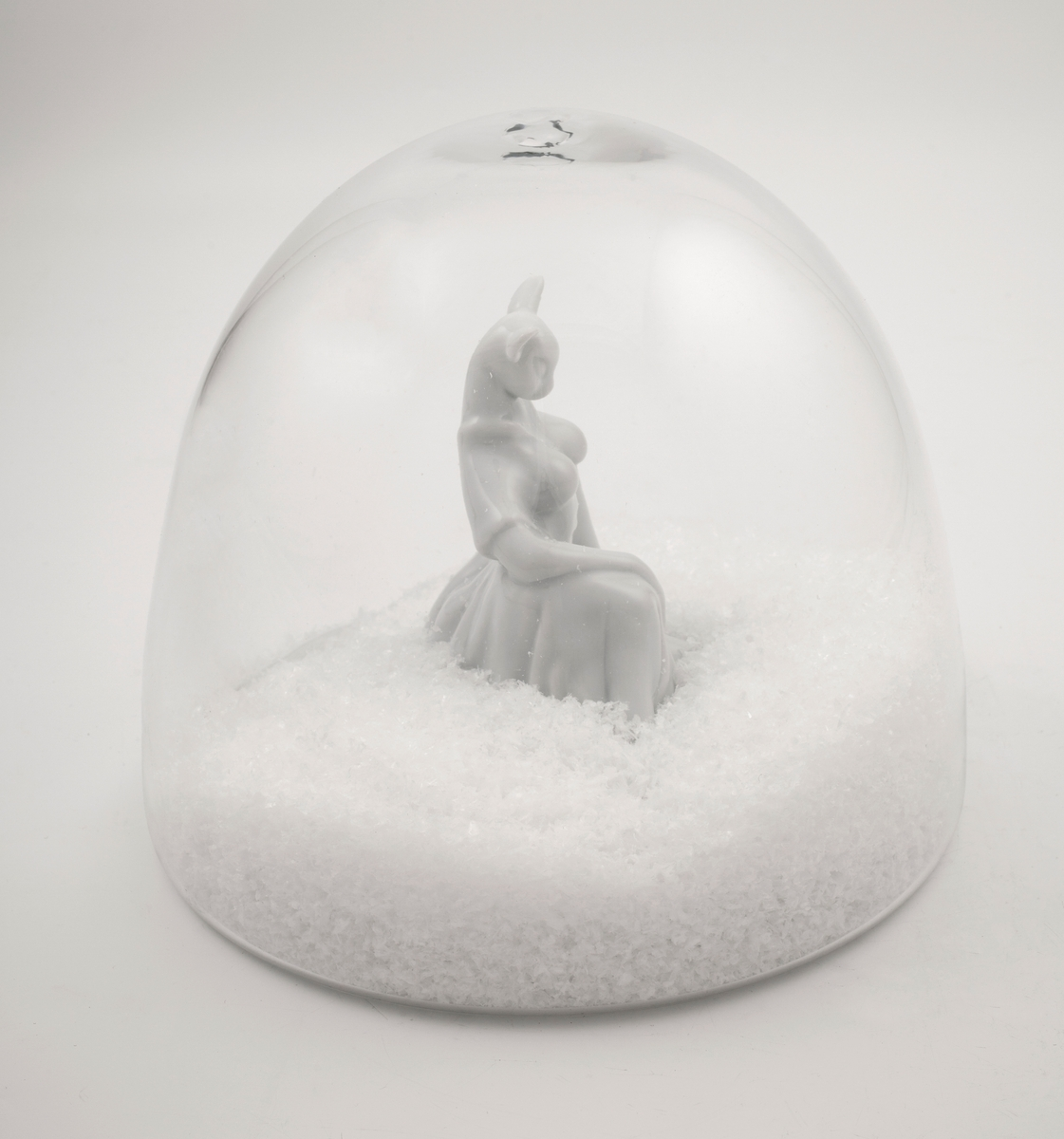 Hvit porselensfigur med rådyrhode og menneskekropp, plassert i omsluttende glasskuppel med kunstige snøfnugg.