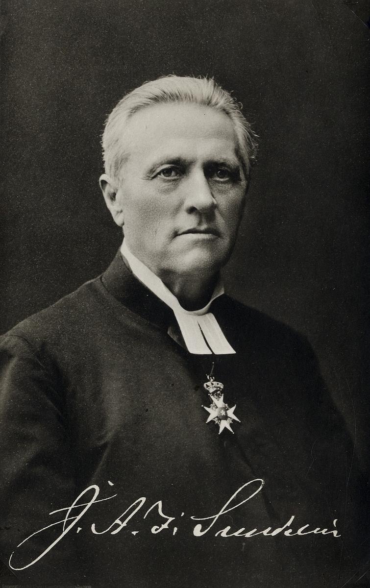 """Foto av en man klädd i prästrock och prästkrage. Under prästkragen syns Nordstjärneorden i band.  Under fotot syns en autograf: """"J.A.I. Sundelin"""".  Bröstbild, halvprofil. Ateljéfoto."""