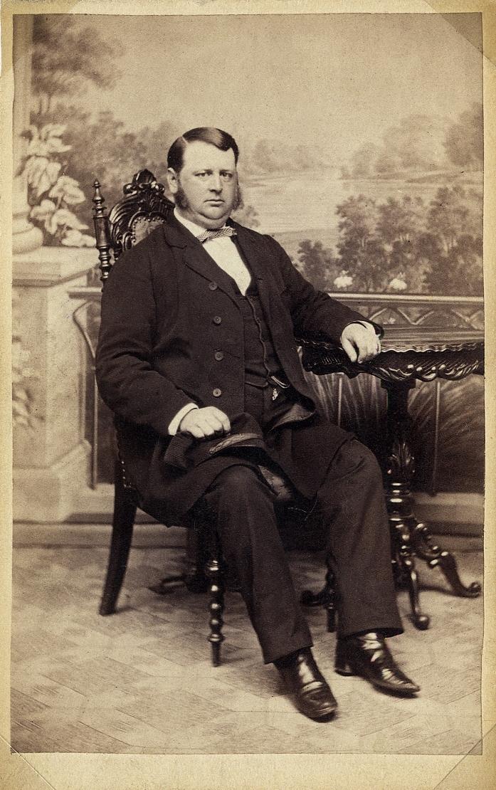 Foto av en man i bonjour med väst och fluga. Han sitter på en högryggad stol invid ett pelarbord. Helfigur, halvprofil. Ateljéfoto.