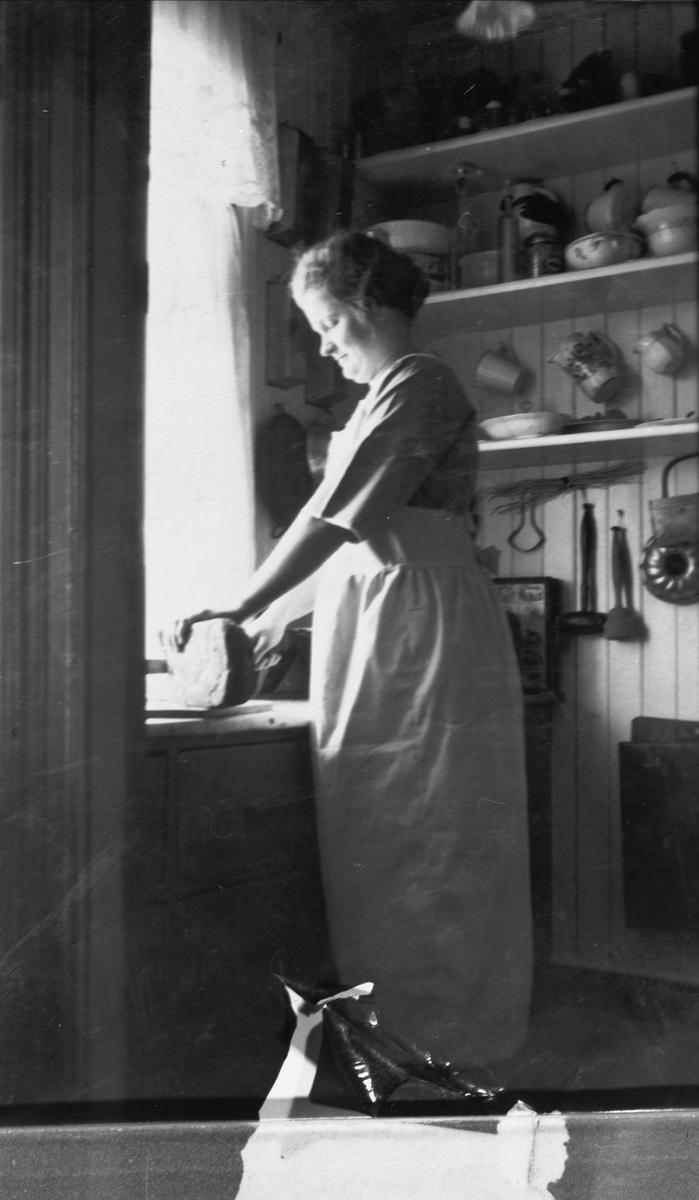 Portrett av kvinne som skjærer brød på et kjøkken.