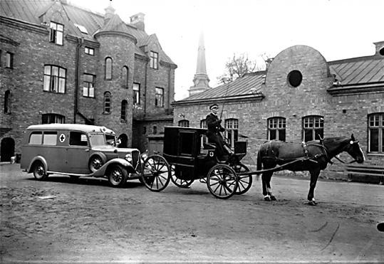Ambulans och epedemivagn från sidan, utanför Västerås brandstation.