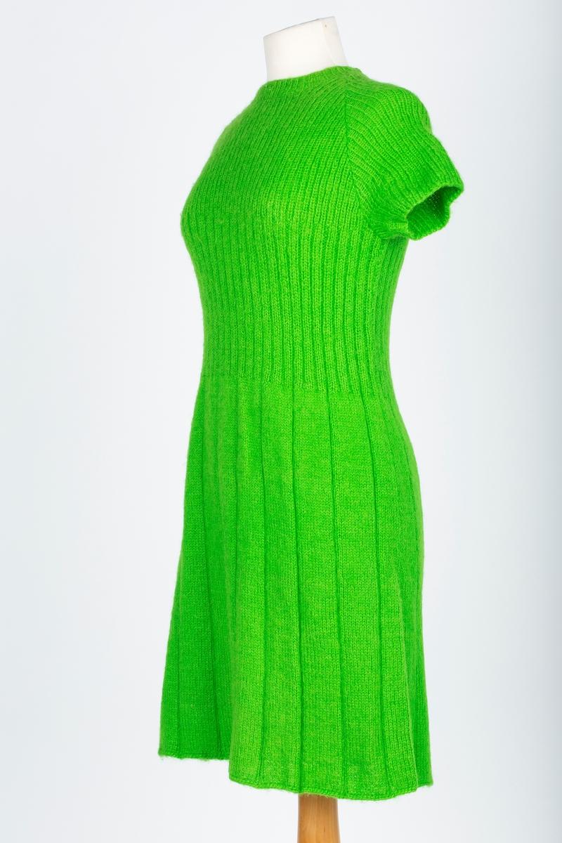 Kjole. Håndstrikket. Rund halsringing. korte ermer. Srtikket i 2 bredder og sydd sammen. Svakt skrådde sider (12 rette 2 vrange), 21 cm høyt mageparti medd 2 r2v og brystparti, ermer og halskant strikket med 1r og 1 v. Isydde raglanermer. Produsent er ukjendt.