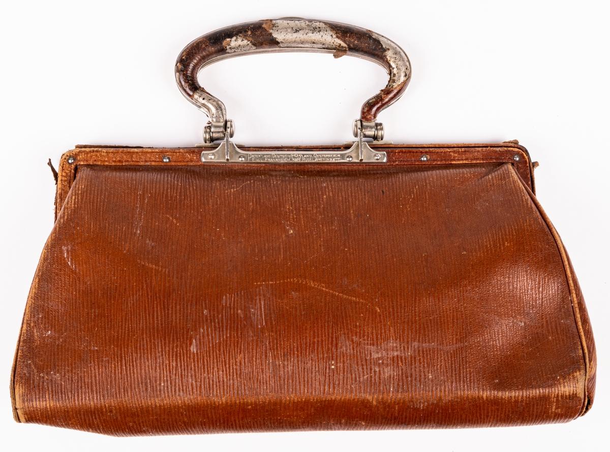 Handväska i ljusbrunt skinn med kluven bygel. Låset placerat i bygeln.
