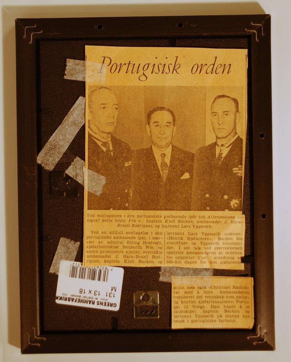 Fotografi i sort plastramme  med glass. Avisklipp festet på baksiden.