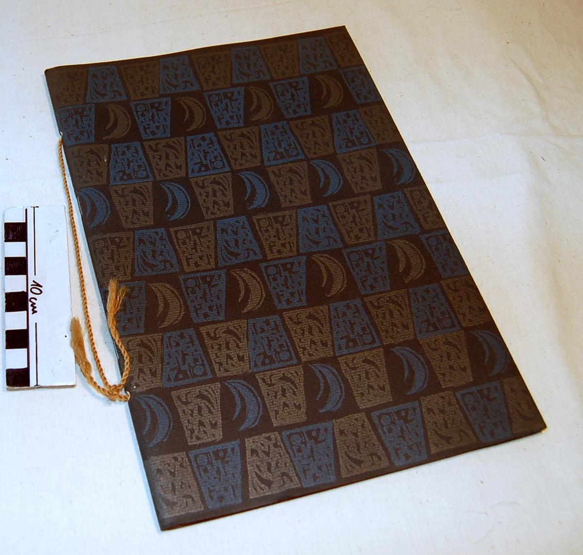 Blått og brunt stilisert mønster på juleheftets omslag