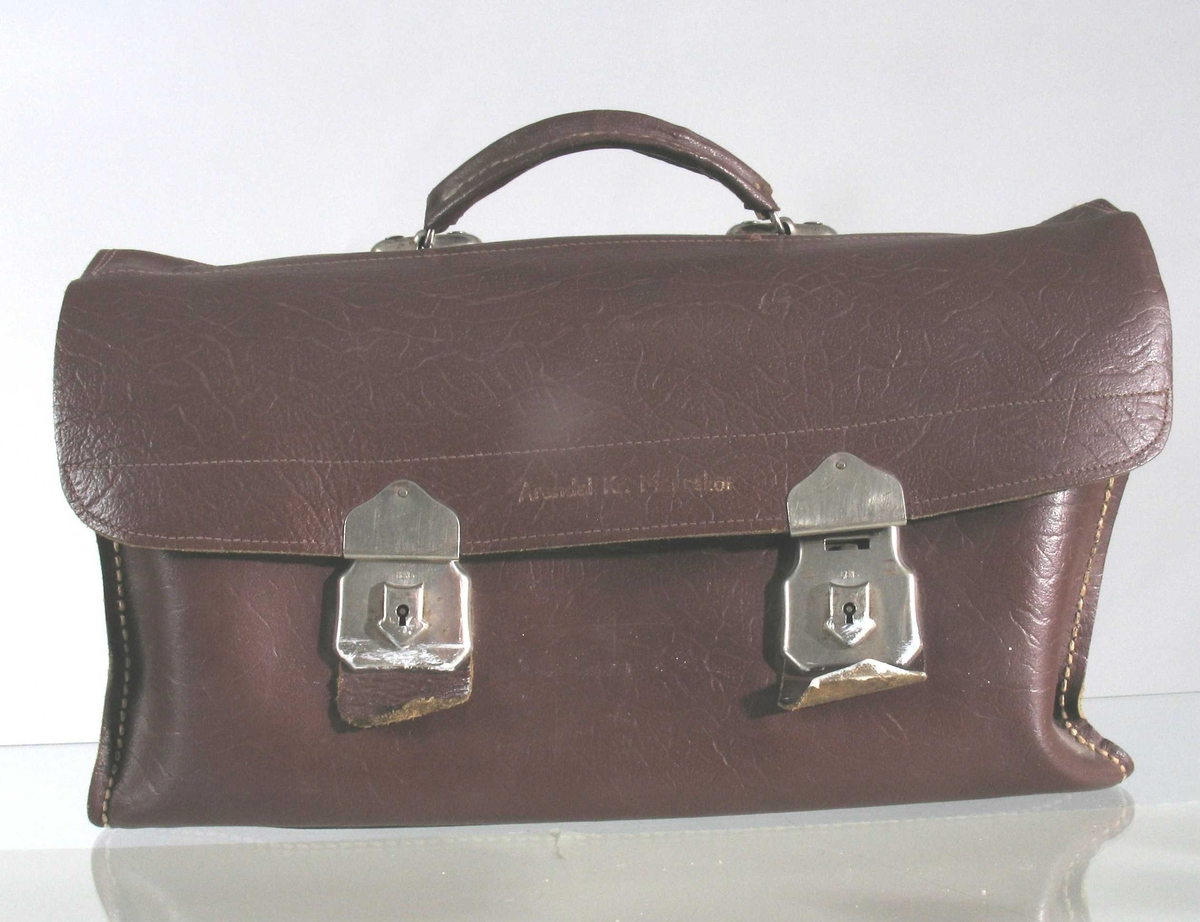 Postveske-lokk. Et håndtak på toppen, 2 rom innvendig, 2 låser på fronten. 2 nøkler festet på innsiden av veska.
