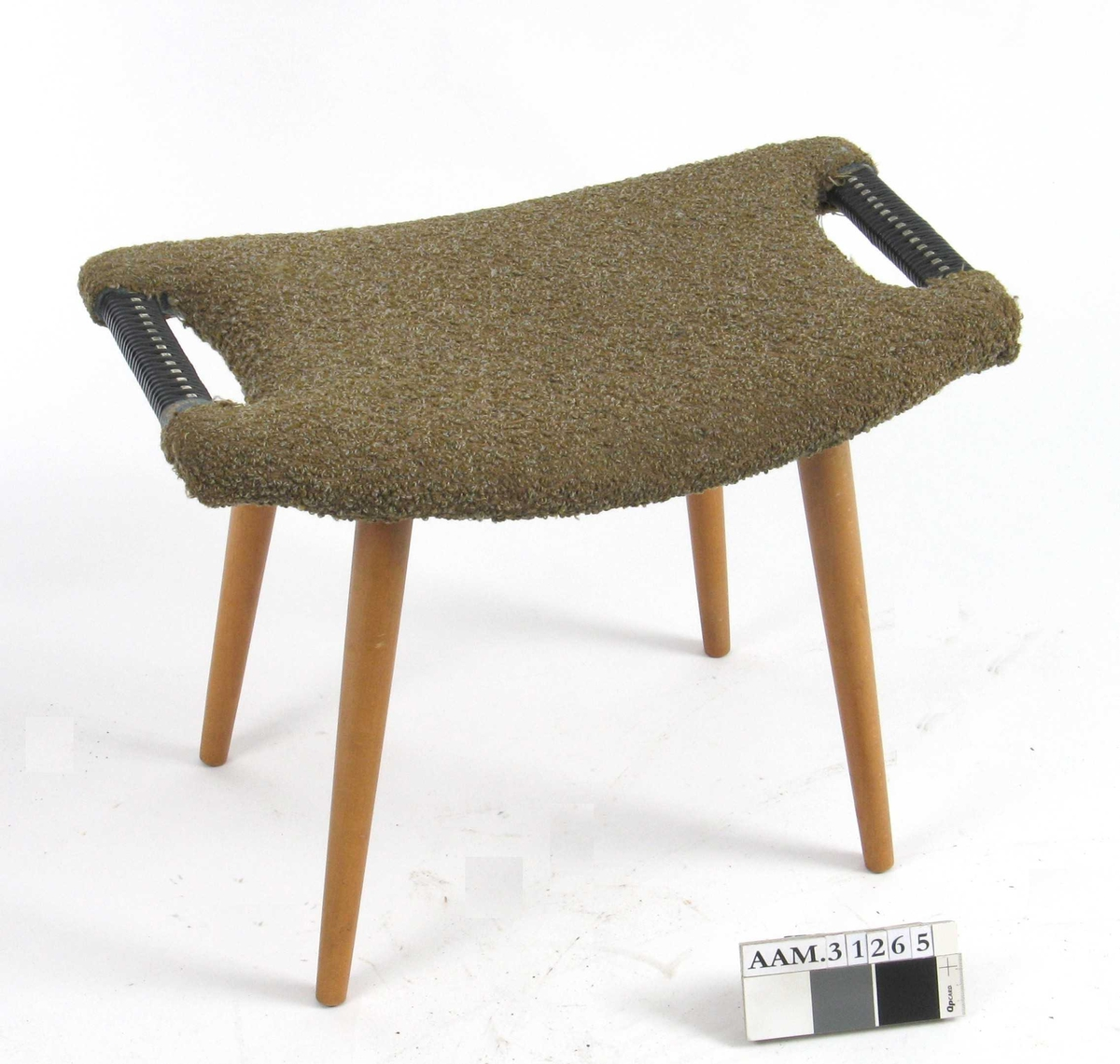 Krakk med tynne bein, rektangulær sitteflate, svakt buet, håndtak i hver kortende, stofftrukket sete.