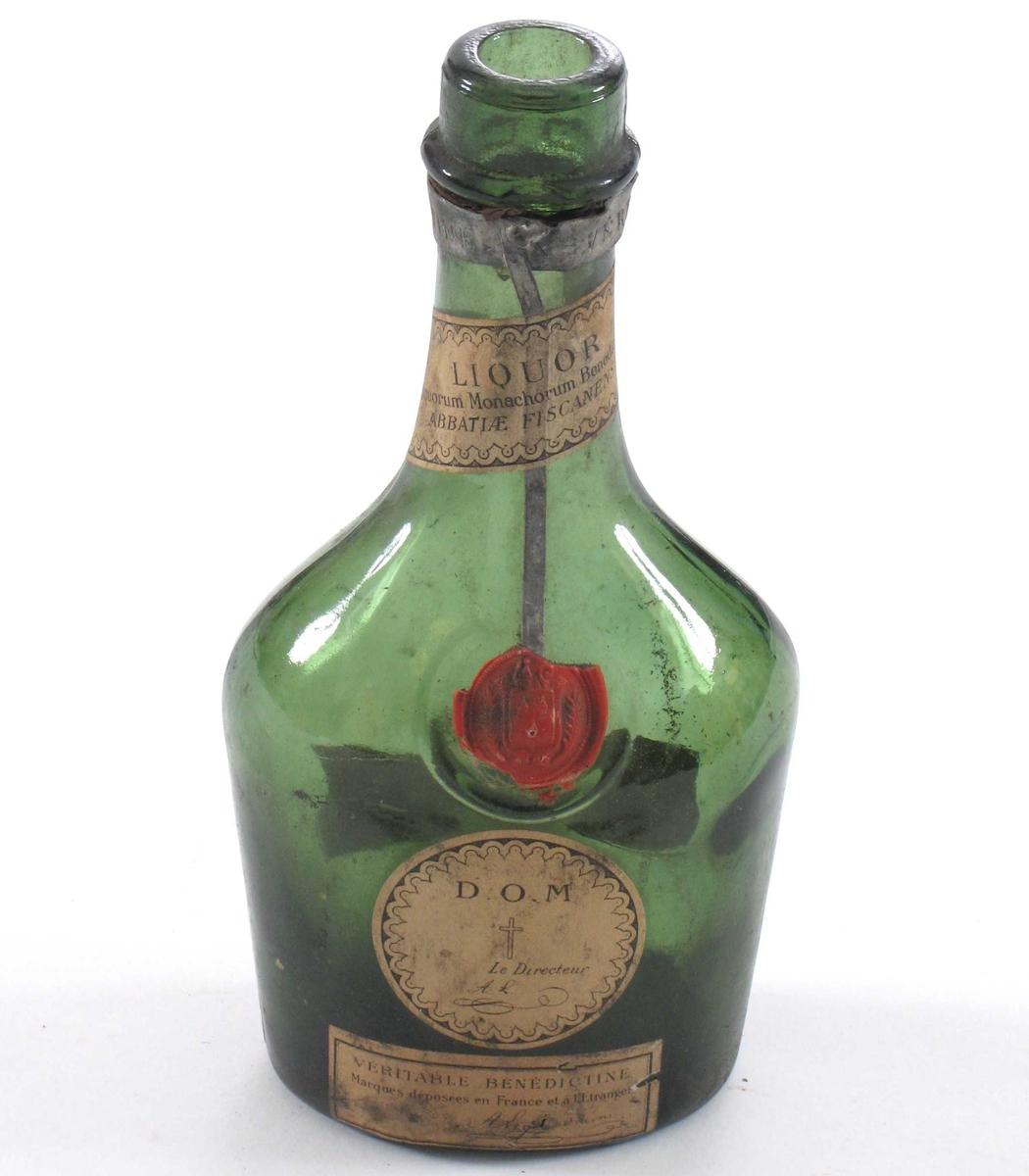 """Flaske med oval bunn, lav """"kropp"""" og lang hals. Rest av forseglingsstempel av lakk."""