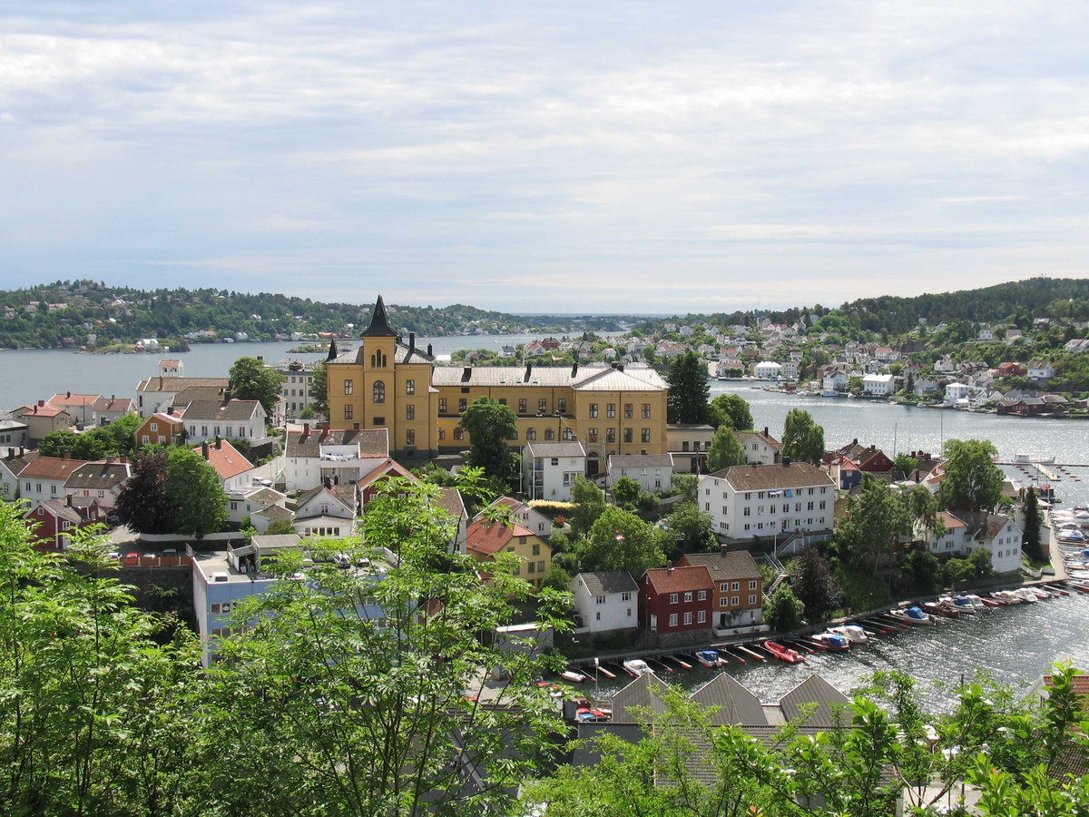 """Øvre del av Tyholmen sett fra Høyveien. Arendal gymnas, """"Borgen"""" dominerer. Galtesund i bakgrunnen."""