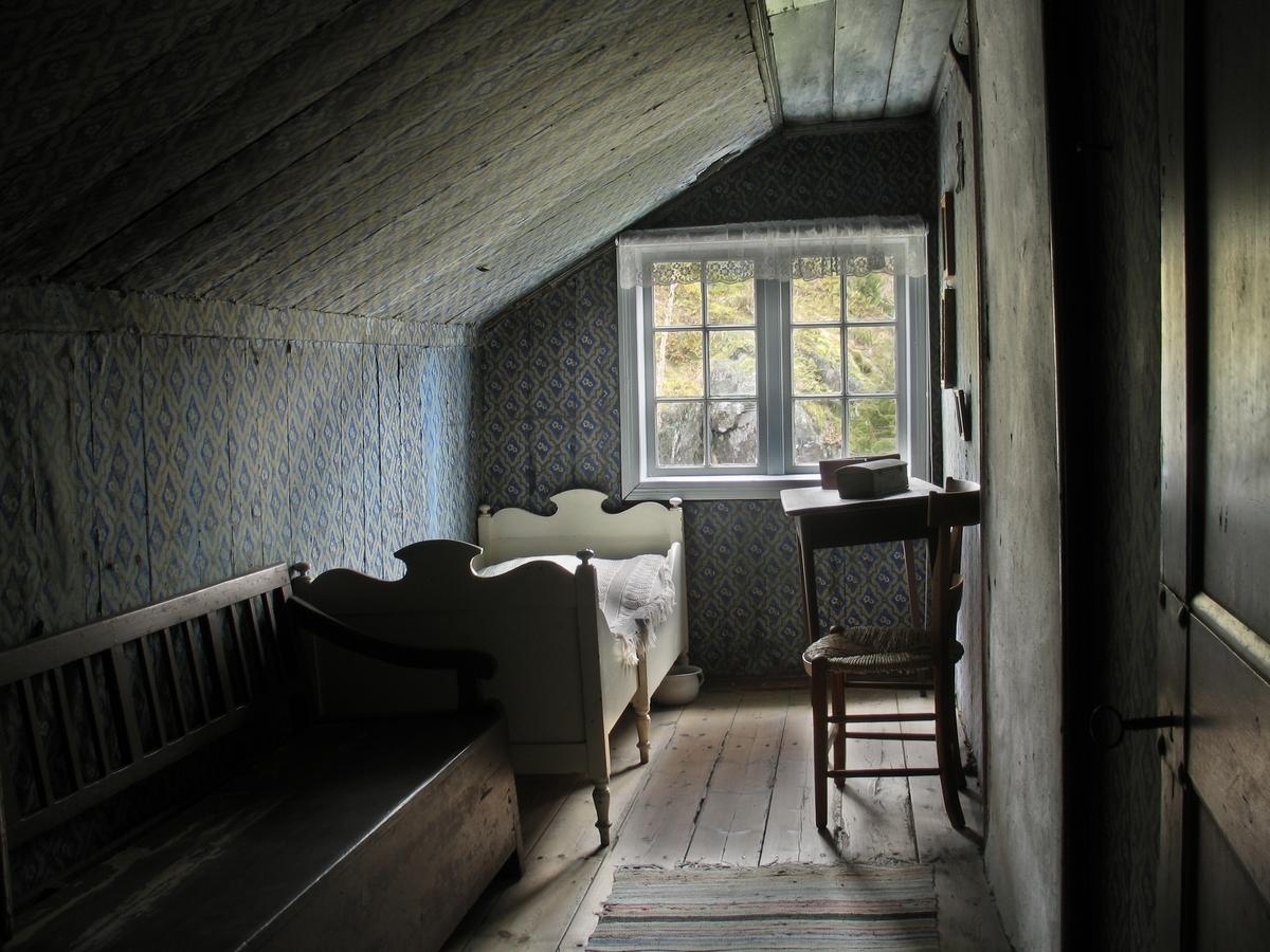 Merdøgaard. Interiør Blåkammerset  i 2. etg. Loftsrom i svalgangens ende, skråtak over det meste av rommet. Var tjenestejentas rom. Seng, stoler, vindu.
