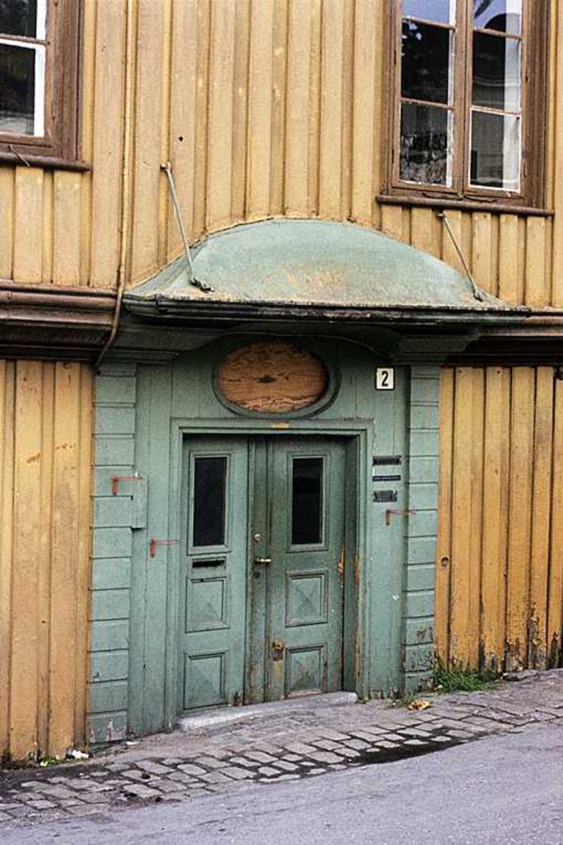 Inngangsportal til det gamle politikammeret. Portal i grønnt, oker husfasade.