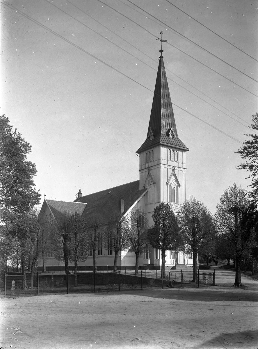 Grimstad kirke  Rester etter den gamle kirkegården sees nede til venstre.