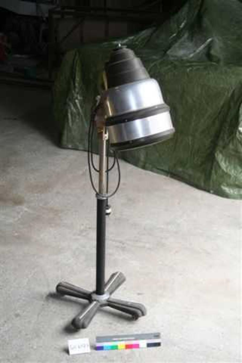 Form: Loddrett stang med fire bein m.hjul. Justerbar kapsel