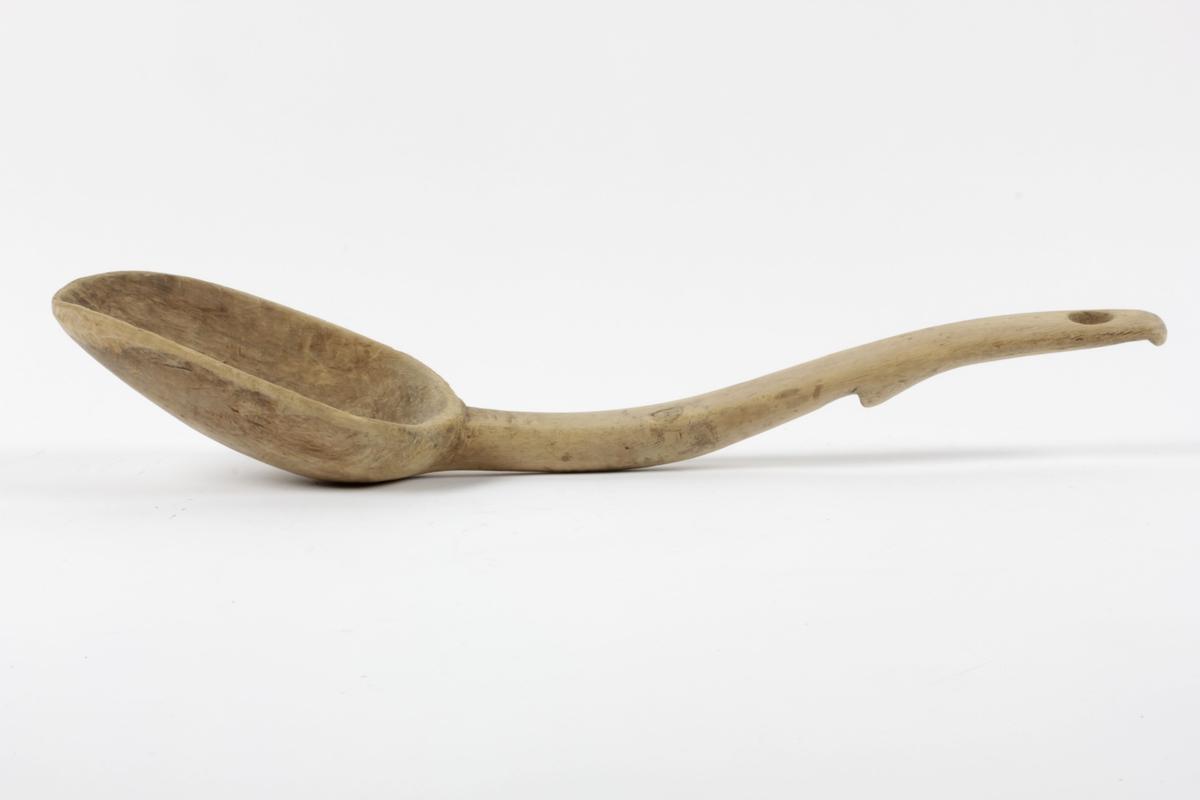 Ause med dypt utskåret blad. Skaftet har et innskåret hakk et stykke over midten, og et sirkulært gjennombrutt hull øverst. Kanten skåret med en vulst under