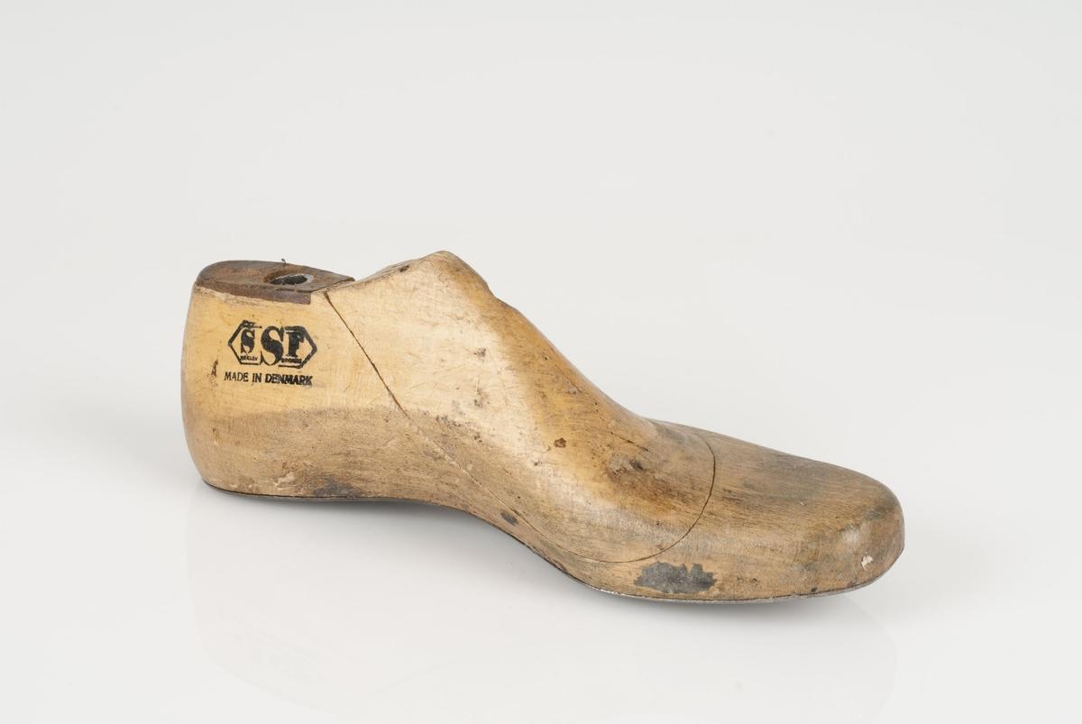 En tremodell i to deler; lest og opplest/overlest (kile). Venstrefot i skostørrelse 37, og 8 cm i vidde. Såle i metall.