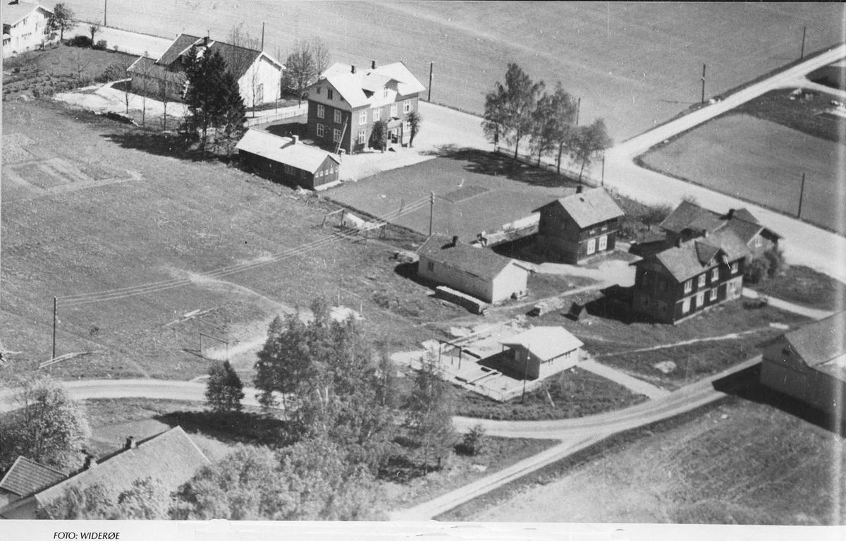 """Brødrene Eriksens Landhandleri, Berggårdene og """"det blå huset"""" (tidligere gamlehjem) sett fra høyre mot venstre i bildet."""