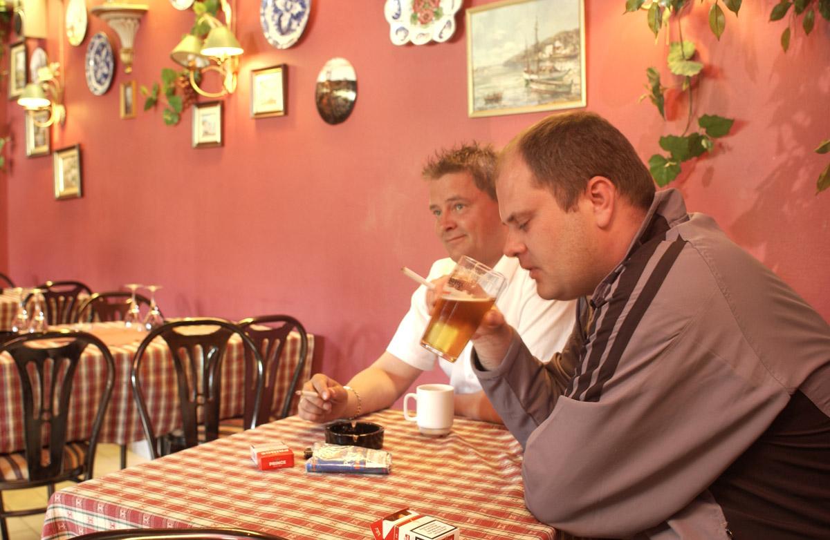 La Casita, inne i restauranten ved et bord. Sigaretter, askebeger, kaffe, og øl på bordet. To menn som røyker