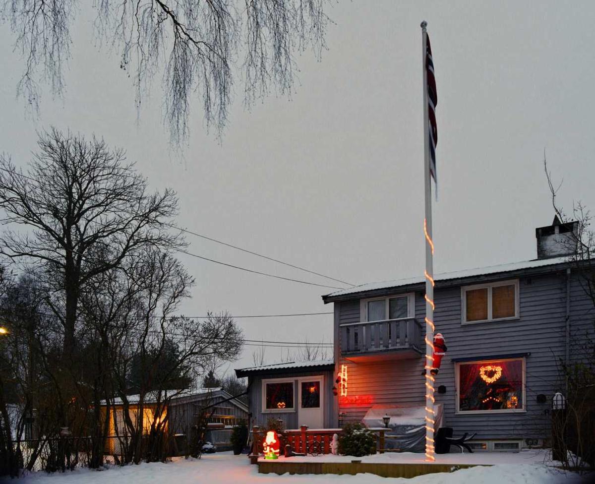 Julebelysning.    Flerfarget julebelysning på enebolig.Flerfarget ysslange og klatrende nisse på flaggstang. Lysende nisse på veranda og klatrende nisse på lysende stige på husvegg. Lysende krans i vindu.