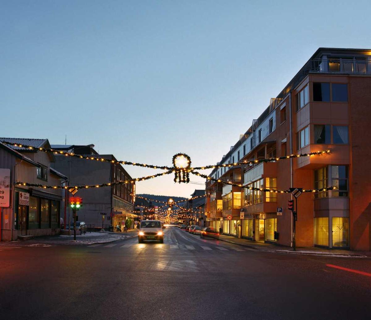 Julebelysning.  Julegata i Lillestrøm. Granbar med hvit julebelysning og midtdekorasjon hengende slik at belysningen danner allèeffekt med avsluttende gran for enden av Storgata som fondmotiv