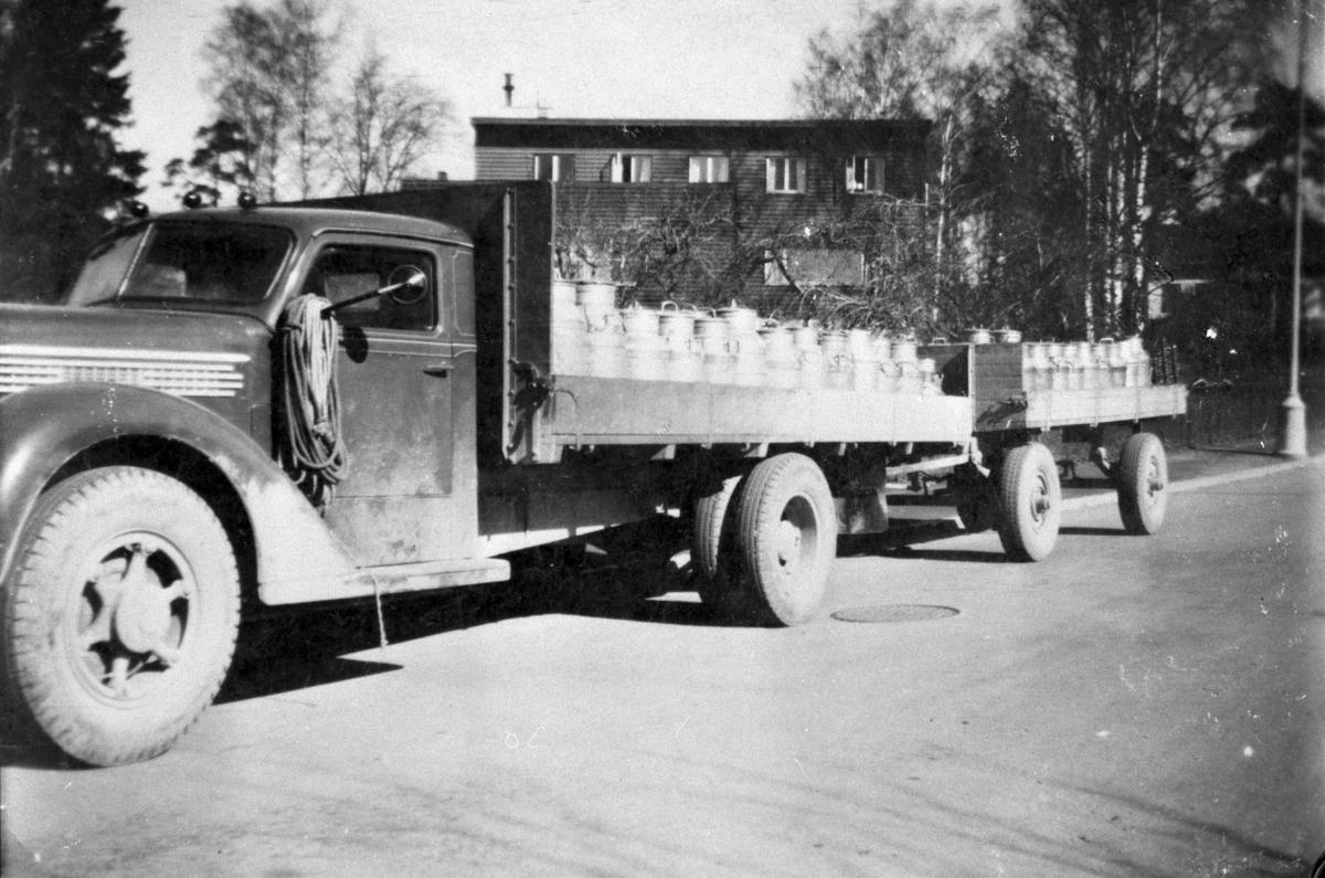 Lastebil med tilhenger, mjølkebil med mjølkespann i Furnesvegen i Hamar. Levering av mjølk til Melkefabrikken. Lars Ulvens lastebil Diamond T, årsmodell 1938-39, med orginalt amerikansk førerhus. Lars Ulven kjørte mjølkerute fra Moelv til Hamar etter krigen