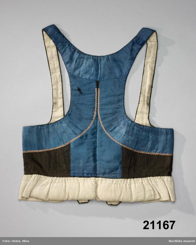 Livstycke med djupa hals- och ärmringningar och smala axelband. Av svart bomullsatin, och 6 cm breda blå sidenband som täcker merparten av livstycket. Banden lätt rynkade vid de ringade partierna och vid inre kanterna en smal dekorsöm i flätsöm med rosa och vitt silke. I framkanterna tillsydda flikar av det svarta tyget, knäppning med 2 par hakar och hyskor av mässing. Foder av oblekt linnelärft. I nederkanten påsydd 5,5 cm bred dubbelvikt remsa av oblekt linnelärft som bak är stoppad till en valk, denna är delad med ett sprund mitt bak. Denna del stoppas innanför kjolen. I den nedre rundade delen av halsringningen sitter 3 par maljor av silver, vars mönster bildar monogrammet AF.  Anm. Sidenbanden sköra och trasiga på några ställen. Maljorna stämplade; möjl. JH = Johan Petter Hasselgren i Lund, verksam 1848-1875. Livstycket kommer från Svedala socken som vid tiden för livstyckets användande hörde till Vemmenhögs hd, först 1867 överfördes socknen till Oxie hd. /Berit Eldvik 2008-02-28