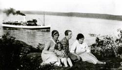To kvinner, en mann og et barn sitter på bakken med ryggen m