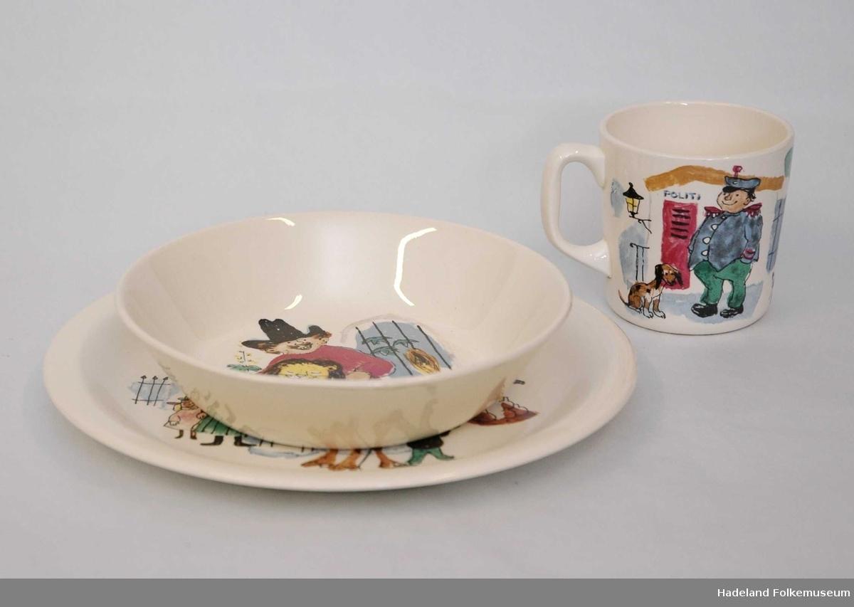 """Flat tallerken, dyp tallerken og kopp i hvitt steintøy med fargerik dekor: motiver fra """"Kardemommeby"""" av Torbjørn Egner. Eske med Egners tegninger og teksten til sjørøvervise."""