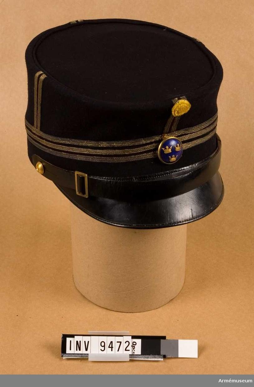 Svart kläde, med skärm och rem av lackerat läder. Remmen är fäst med två guldfärgade obottnade knappar (artilleri) i vardera sidan, samt försedd med spänne utan torn. Tre guldgaloner kring kullens nedre del (vardera 0,5 cm breda). Stolpar, bestående av två guldgaloner (vardera 0,5 cm breda). Mitt fram officersknapp i guld och blå emalj m/1865 och överst på stolpen en gul sidenkokard. Brun svettrem. Svart foder. Stöd under stolparna, innanför fodret, för att hålla kullen styv. På kullens insida finns uppmärkt ett C (guldfärgat) med två punkter (guldfärgade); en på vardera sidan om C:et. Tyget är nött framför C:et, varför det troligen även där har funnits en bokstav. Vänstra stolpen fransig i nederkanten.Jean Charpentier är Torstens fader.