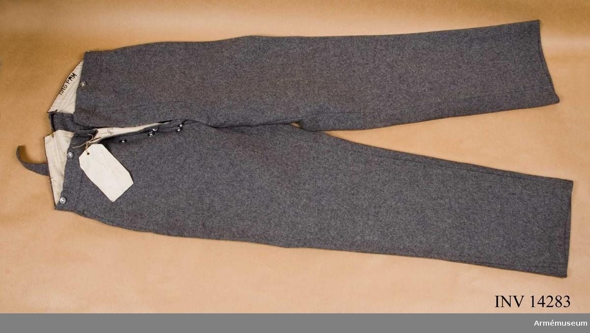 """Grupp C I. Regemente oberidet artilleri. Byxor, da. bukser, av grått kläde, långa med två fickor på sidan och på baksidan, spänntamp av kläde med spännen. Järnknapparna är tre par på sprundet och sex dito för hängslen. Foder av vitt tyg med stämpel """"PRM"""" - prövemaessigt, modellenligt. """"1916"""". (Munderingsvaesenet i Fedstid 1:a Hefte, Kjöbenhavn 1908 sid 30 paragraf 54. Byxorna har en papperslapp, på vilken det står """"Benkläder for überedent Artilleri Störrelse 186 cm"""".Litteratur: Enl Handbuch der Uniformkunde, Prof. R Knötel-  Sieg, Hamburg 1937, sid 142. Under världskrigets lopp (1914-1917) infördes i denna armen uniform av stengrått kläde."""