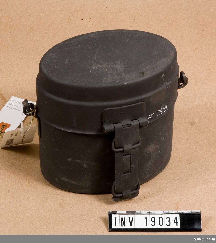 Av rostfri plåt, målad  gråsvart. Överdelen (locket) har handtag och rymmer 0.7 liter (till falsen 0.25 1.) På handtaget finns öglor där man kan träda in en knäpp om man vill steka över öppen eld. Underdelen rymmer 1.5 liter (till falsen 1.31.) och har hank och krok och därför lämpligast att värma mat i.Kärlet ingår i personlig utrustning i alla försvarsgrenar.