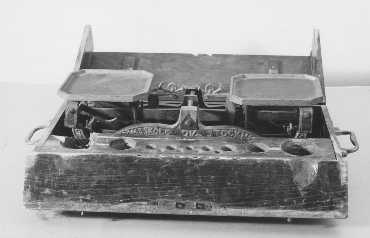 Våg, av så kallad taffelvågstyp, i låda av trä. Med vågskålar som bärs upp av ståndare och står lodrätt över balansen. På den ena skålen läggs brevet som ska vägas och på den andra vikterna. Är vågen riktig intar balansen ett horisontalt jämviktsläge när brevet och vikterna är lika tunga. Inskription: Sjöström & Sköld, Stockholm, 3 kg.