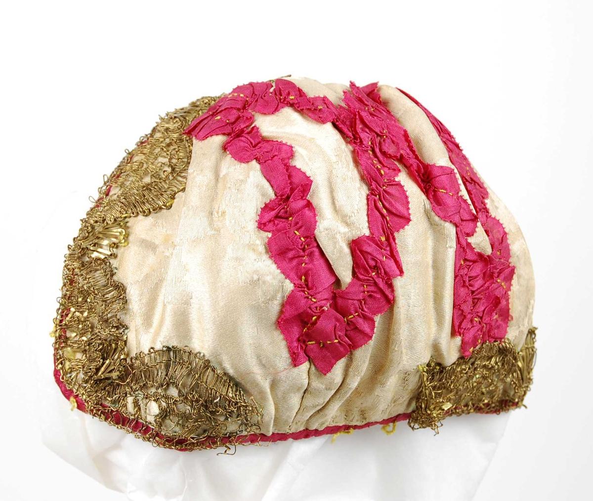 Lue i tre deler: midtstykke fra panne til nakke, et trekantet avrundet stykke mot midtstykket på hver side. Lua er sydd av rosa silkedamask, kantet med rød silke og fôret med bomull. Dekor av rødt silkebånd påsydd med gul tråd og kantet med gullfarget metallblonde. Blonden mangler et stykke på 4 cm midt bak.