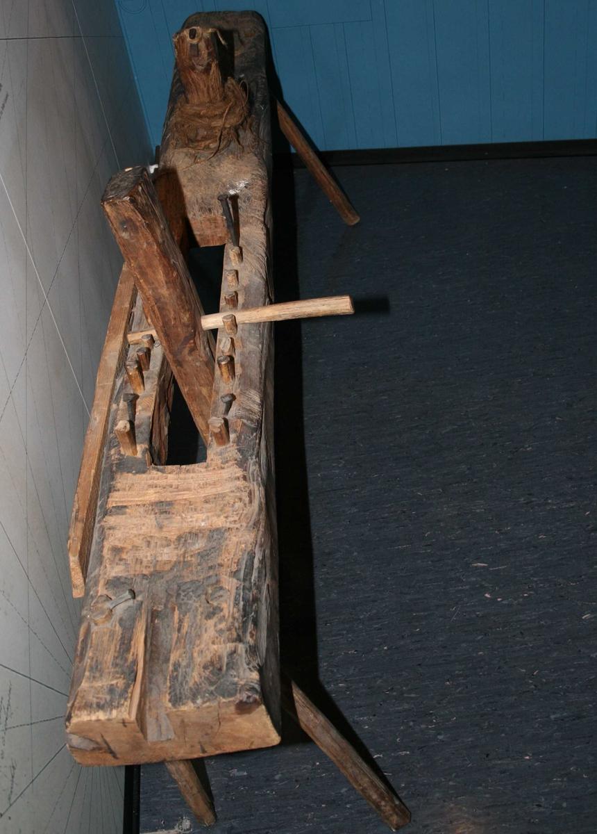 Kraftig planke med to skrå ben i hver ende, i  den ene halvdel åpen spalte med tverrstilt  planke med   jern  tapp øverst, stillbar etter  trenaglenes lengde. Ved midten et fast make vertikalledd, med jerntapp, og surret med filler  og tau.  Ble brukt når en skulle lage trenagler  til skutene. Arbeideren satt på tvers.