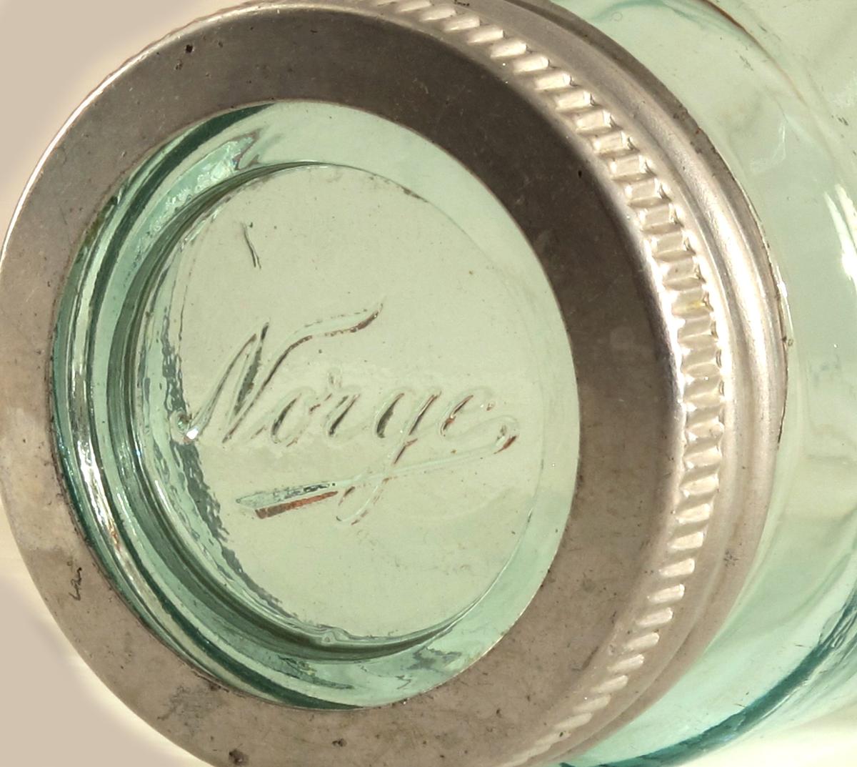 """Norgesglass,  hermetikk glass.  syltetøyglass    Glass,  grønnlig. Ustemplet, antag. Moss Glassverk.   3/4 liter   syltetøy eller hermetiseringsglass   sylindrisk  med noe smalere munning skrugjenger.   Norge  i relieff  på siden. Skrulokk av aluminium  med åpent midtparti, underliggende  glass-skive med """"Norge i relieff.  Har hatt rød gummiring, pakning, som ble lagt  på for å gjøre lokket helt tett."""