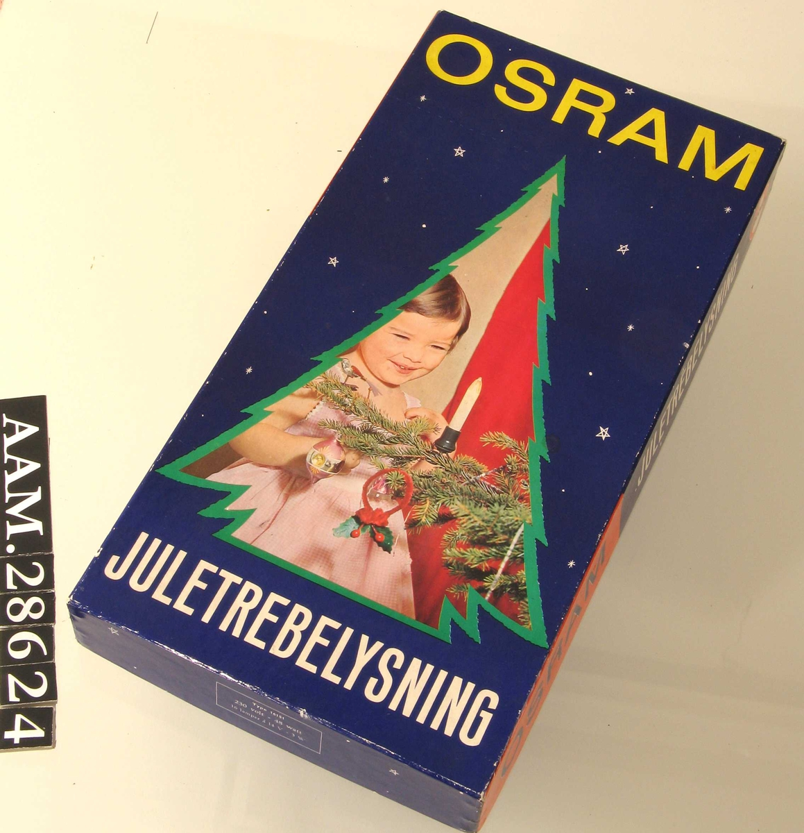 På eskens lokk et utsnitt av et fotografi; ei lita jente som beundrer et elektrisk julelys montert på en grankvist: