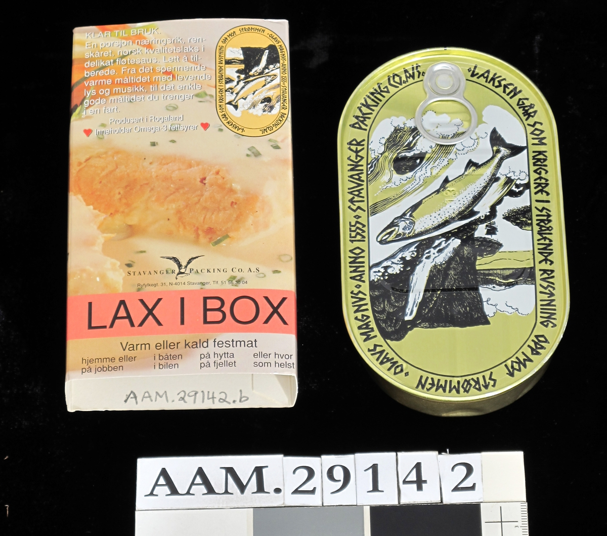 På metallboksen tegning av laks som hopper i en foss, med Prekestolen som silhouett i bakgrunnen. På kartongen fotografi i av laksekjøtt i saus.