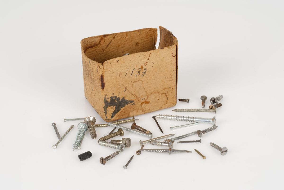 Spiker og skruer av stål/metall i forskjellige størrelser. Spikerene og skruene ligger sammen i en pappeske. En hvit og blå merkelapp på undersiden av esken som er slitt.