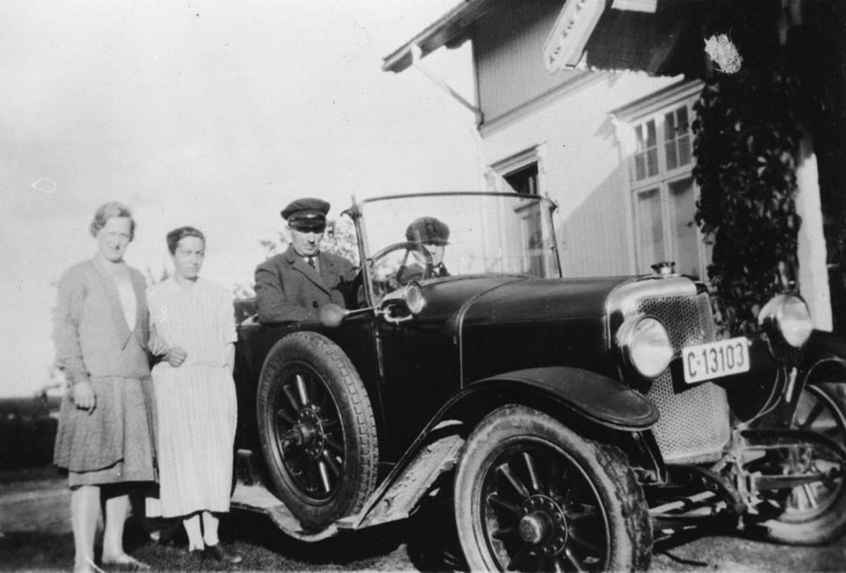 To menn sittende i bil, to damer står ved siden av.