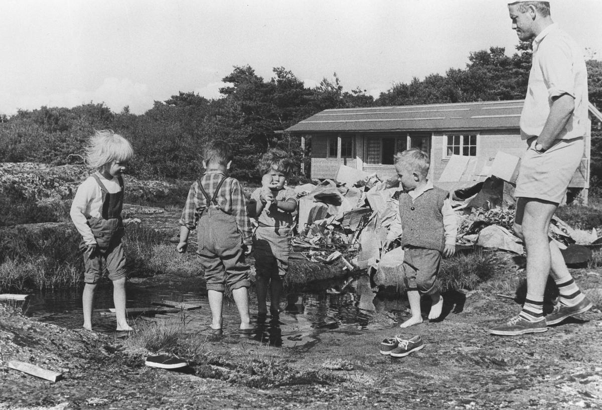 Barn leker i damm utenfor nybygd hytte.