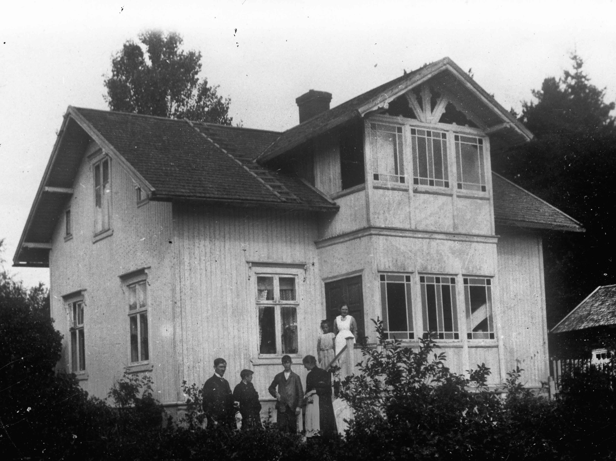 Mennesker foran et hus.