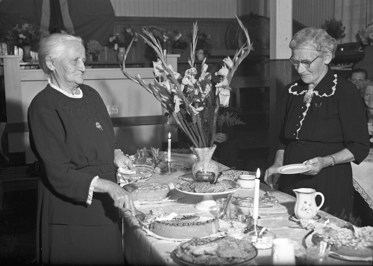Eldre kvinner ved kakebordet.