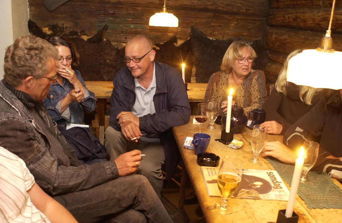 Siste time før røykeloven trer i kraft. Mennesker ved et gruppebord. På bordet er det sigaretter, øl & askebeger. Det Gamle Bageri Ost & Vinstue.