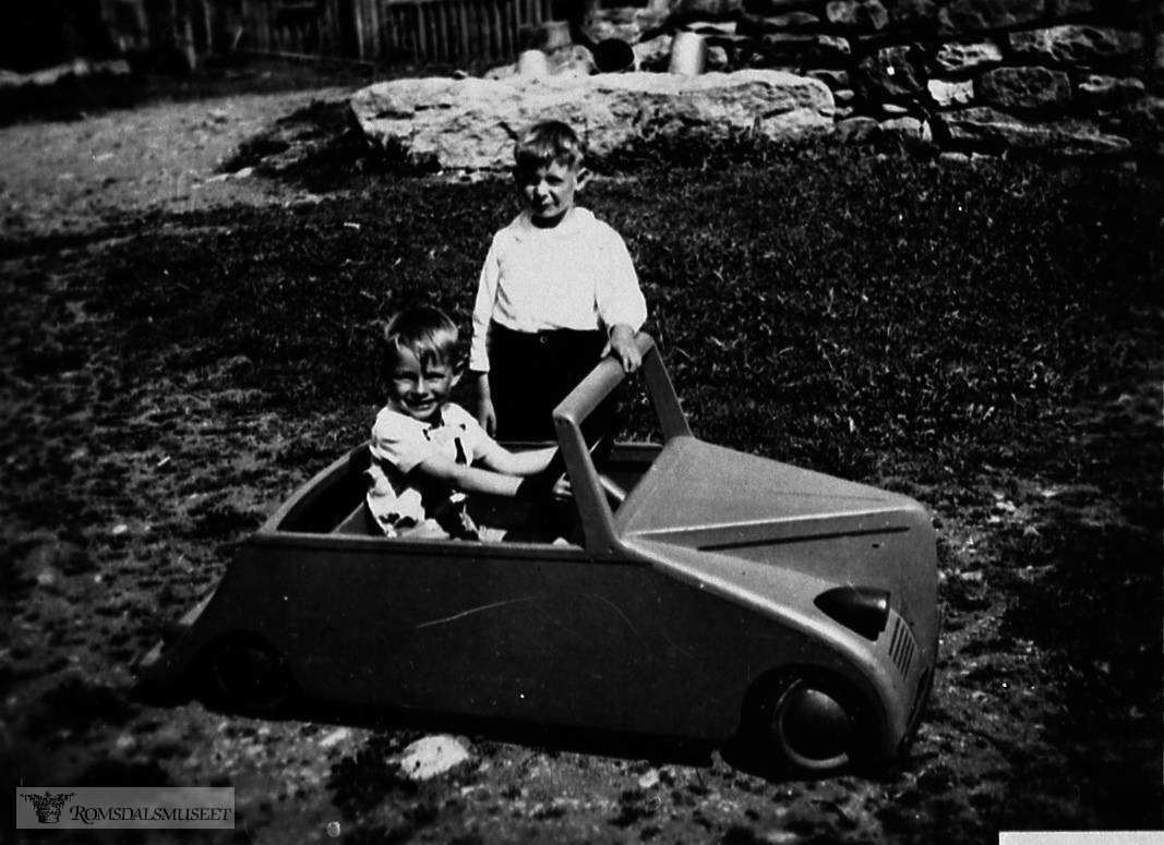 Bjørn Oppigard som sjafør og Tora Oppigard som passasjer i leikebilen. Bilen var laga av Tore Vassli til Bjørn sin 5 års-dag 28.05.1944...