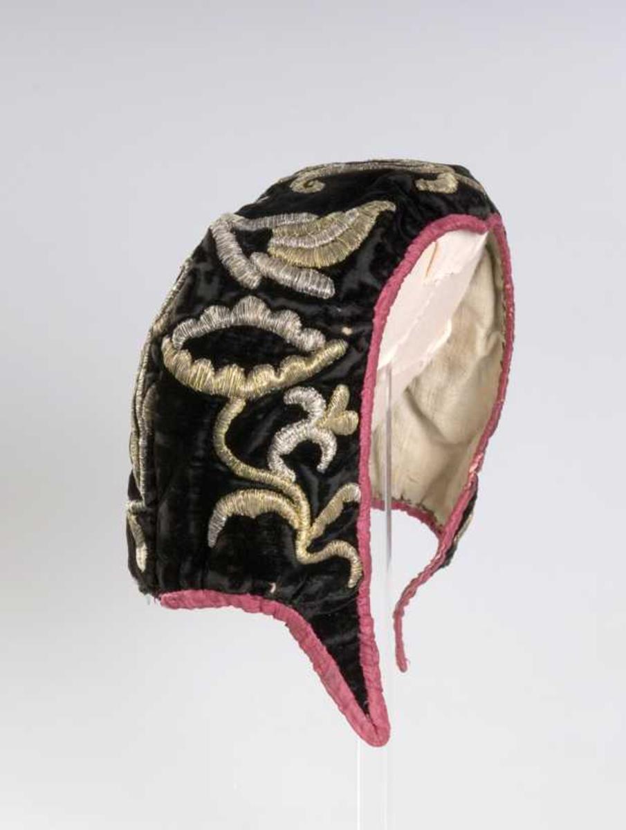 Pullue i svart fløyel m broderi i sølv og gull. Lua er kantet med cerisserød silke. Fôr av lin.