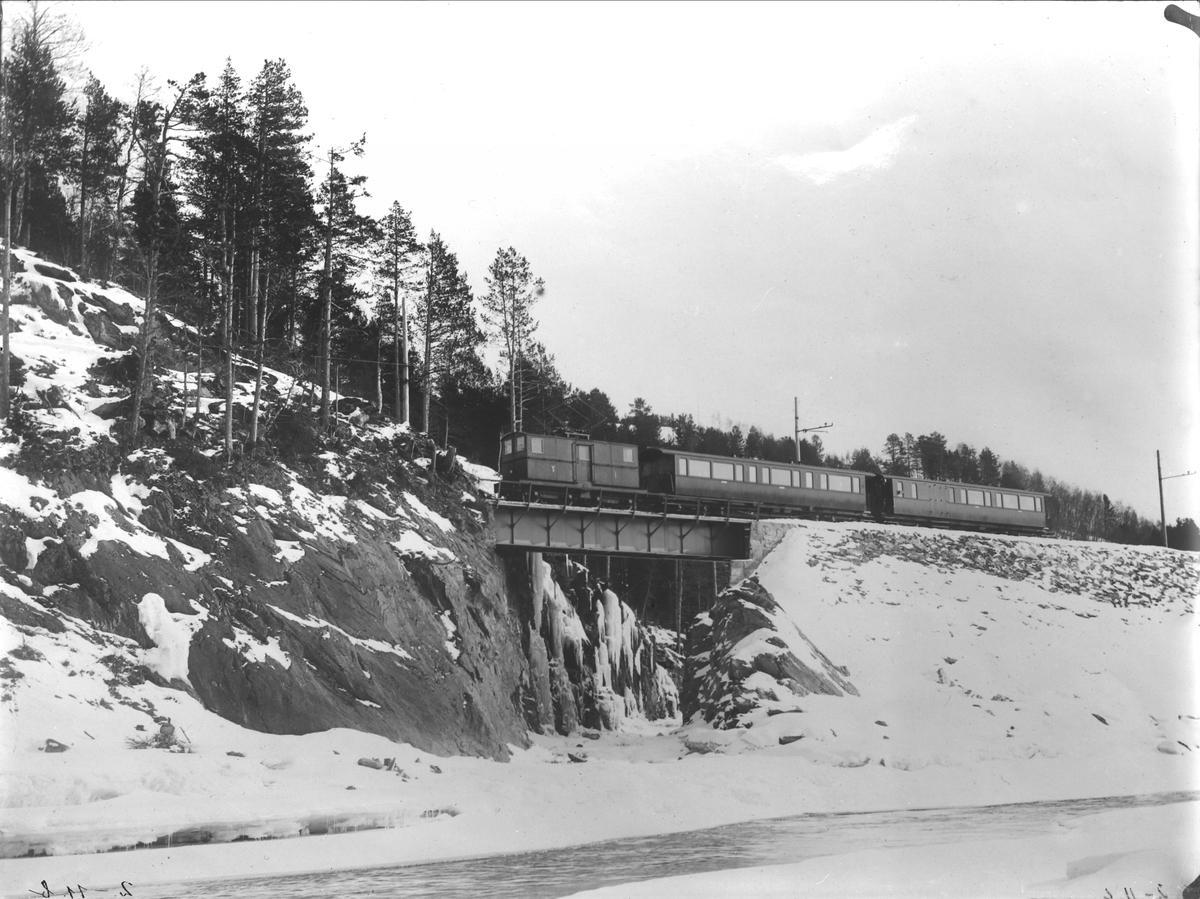 Westinghouse-lokomotiv med to personvogner over Svorka kanal.
