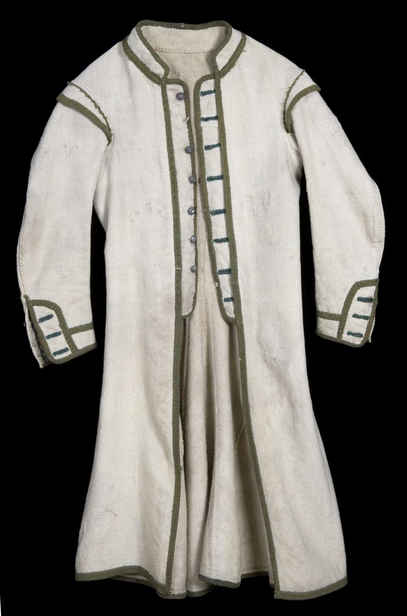 Hvit kjole av ull med grøn dekor av ull. Midjen bak er markert med to garn dusker.